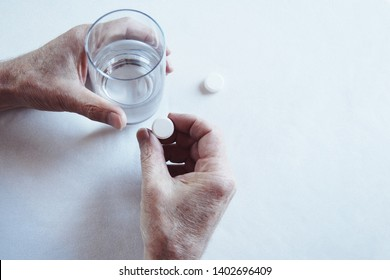 Elderly man hands taking medicine pill with a glass of water. First person view,  light background, cold light