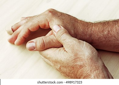An elderly man has pain in his hands