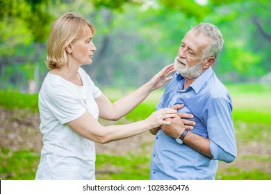 Elderly man have chest pains or heart attack in the park with senior woman, health care concept.