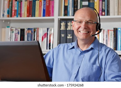 Elderly man with headphones and computer laughing happily, telework, e-business or commerce, customer support representative, video-chat, copy space