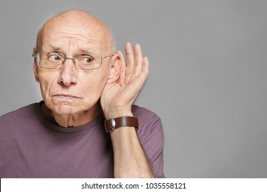 Elderly man with hearing problem on grey background