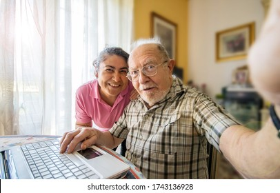 Elderly man with her caregiver taking a selfie photo at home