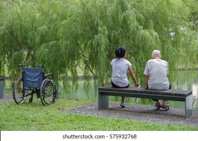 Elderly man and his caregiver on a walk in a park.