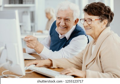 Elderly man and his classmate during computer classes at third age university