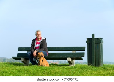 Elderly man with his dog at bench outdoor