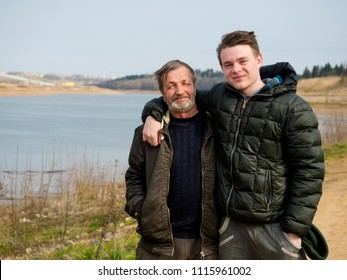 elderly man and his grandson in nature by the river