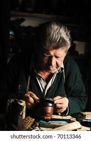 Elderly man in his workshop repairing a shoe