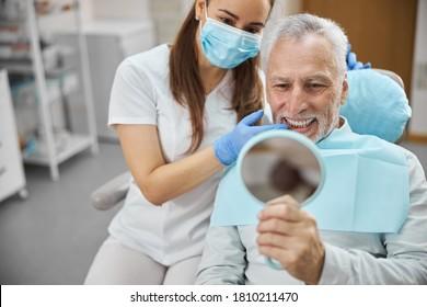 Ältere Männer und ihre junge Zahnärztin lächeln beim Anschauen in den Spiegel in der Zahnklinik