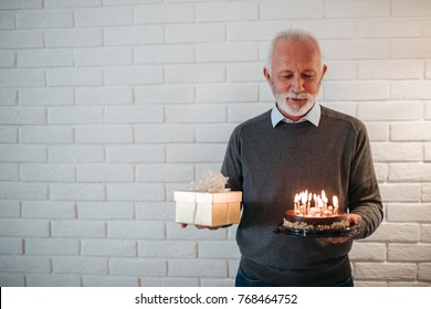 Elderly man holding a birthday cake and a present