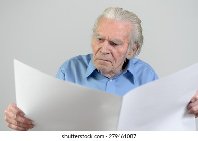 Elderly man holding a blank big white paper sheet and looking at it as at an empty newspaper, portrait