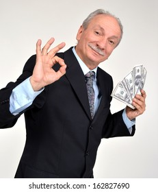 Elderly man holding dollars and showing yes sign