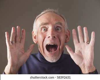 Elderly man holding hands up in horror, screaming