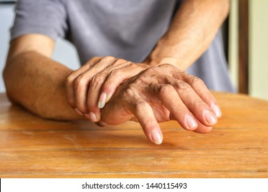 Elderly man is holding his hand and putting on the table because Parkinson's disease.Tremor is most symptom and make a trouble for doing activities such as eat or drink.Health care or elderly concept.