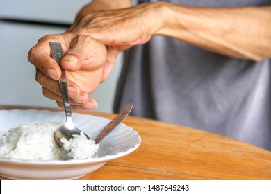 Elderly man is holding his hand while eating because Parkinson's disease.Tremor is most symptom and make a trouble for doing activities such as eat.Health care or elderly concept.Have copy space.