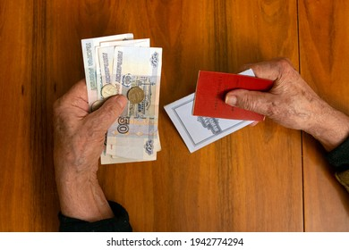 Elderly man holding russian ruble banknotes in one hand and pension certificate with passbook in another. The concept of pension, payment and money savings. - Shutterstock ID 1942774294