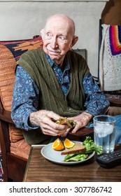 Elderly man holding a sandwich on a TV tray