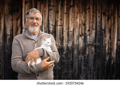 Ein alter Mann hält ein süßes weißes Kätzchen und lächelt der Kamera, selektiver Fokus, viel Kopienraum