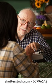 Elderly man in home with care provider or survey taker in kitchen