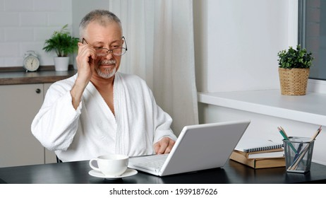 An elderly man in a housecoat is sitting at a computer.