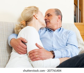 Elderly man hug with mature wife with happiness in home interior