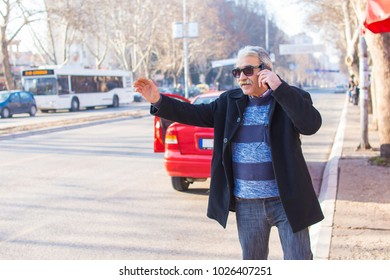 Elderly man in a hurry calling a taxi