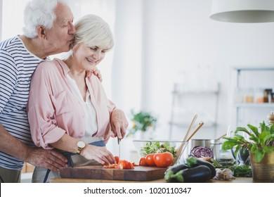 Elderly man kissing wife cutting tomatoe for healthy dinner