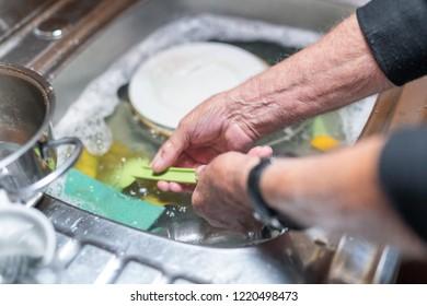 Elderly man in the kitchen washing dishes, detail on hands.