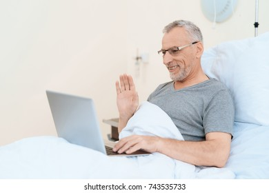 An elderly man lies in a hospital room on a bed. He is undergoing rehabilitation. He has a gray laptop on his lap. He communicates with relatives on a gray laptop.