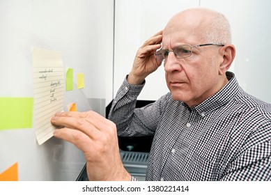 Elderly man looking at notes. Forgetful senior with dementia, memory problem, health concept