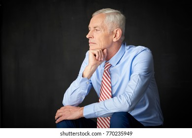 An elderly man looking thoughtfully white sitting at isolated background with hand on his chin.