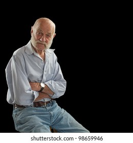 Elderly man looks interested, raises eyebrows, and crosses arms. He is bald with mutton chop whiskers, wears jeans and open-collared shirt. Square composition, isolated on black, copy space.