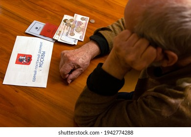 """Elderly man looks sadly at the money and the bill lying on the table. Inscription: """"Unified payment document of Moscow"""". The concept of pension, poverty, payments and rising prices - Shutterstock ID 1942774288"""