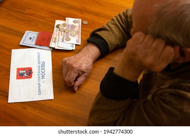 """Elderly man looks sadly at the money and the bill lying on the table. Inscription: """"Unified payment document of Moscow"""". The concept of pension, poverty, payments and rising prices - Shutterstock ID 1942774300"""