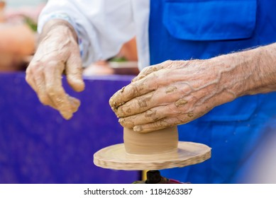 An elderly man makes a jug out of clay, close-up