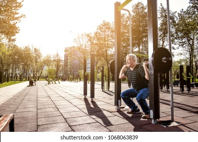 Elderly man making squats with weights in a fitness park (outdoors gym)