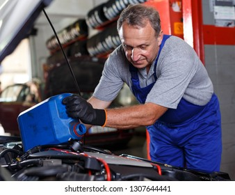 Elderly man mechanic engaged in replacement of engine oil in auto workshop