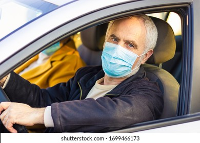 An elderly man in a medical face mask driving a car. Coronavirus pandemic concept. Road trip, travel and old people concept - happy senior couple driving in car