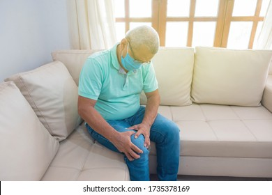 elderly man in medical mask suffering from knee pain at home