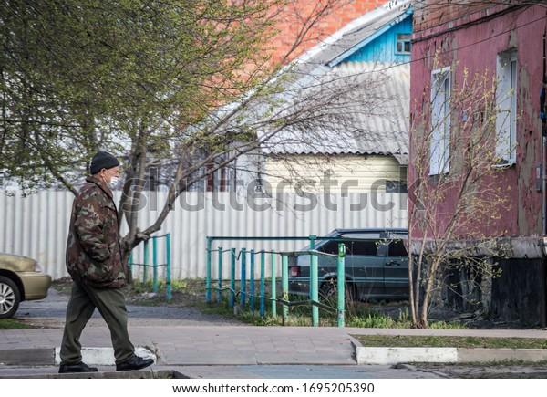 elderly-man-medical-mask-walks-600w-1695