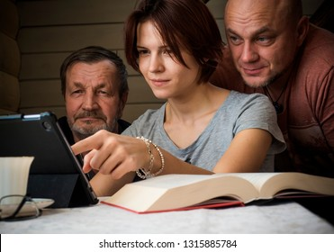An elderly man, middle-aged man and young girl use a tablet computer. Book, cup of coffee and glasses on the table