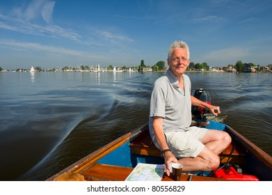 Elderly man is in motorboat at recreational water in Holland
