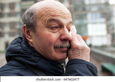 An elderly man with a mustache and bald head wipes tears in his eyes from the wind