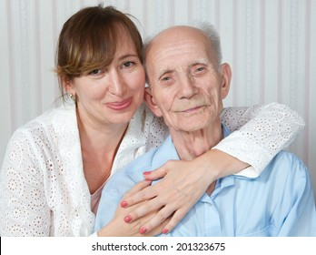 Elderly man and nurse at home. Kind doctor taking care of an old man in wheelchair. Concept of health care for elderly old people, disabled.