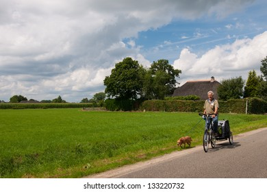Elderly man on bicycle in Holland with walking dog