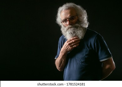Elderly man on a dark background. Senior citizen smortrit into the camera. An old man stroking his beard. Portrait of a gray-haired old man in glasses. Senior citizen with a long gray beard.