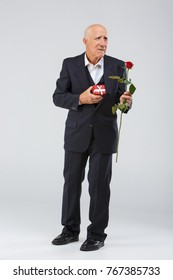 An elderly man on a white background, in the studio, in a black smart suit with a rose in his hand and a red gift box.