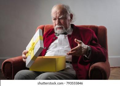 Elderly man opening a present
