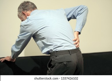 Elderly man with pain in kidneys. Old man with back ache clasping her hand to her lower back. Man suffering from ribbing pain, waist pain.