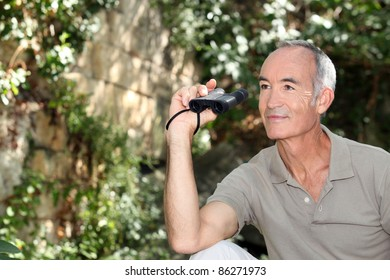 Elderly man in Park with binoculars