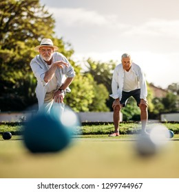 Elderly man playing boules in a playground with his playmate standing in the background. Old man in hat throwing a boules in a lawn with blurred boules in the foreground.